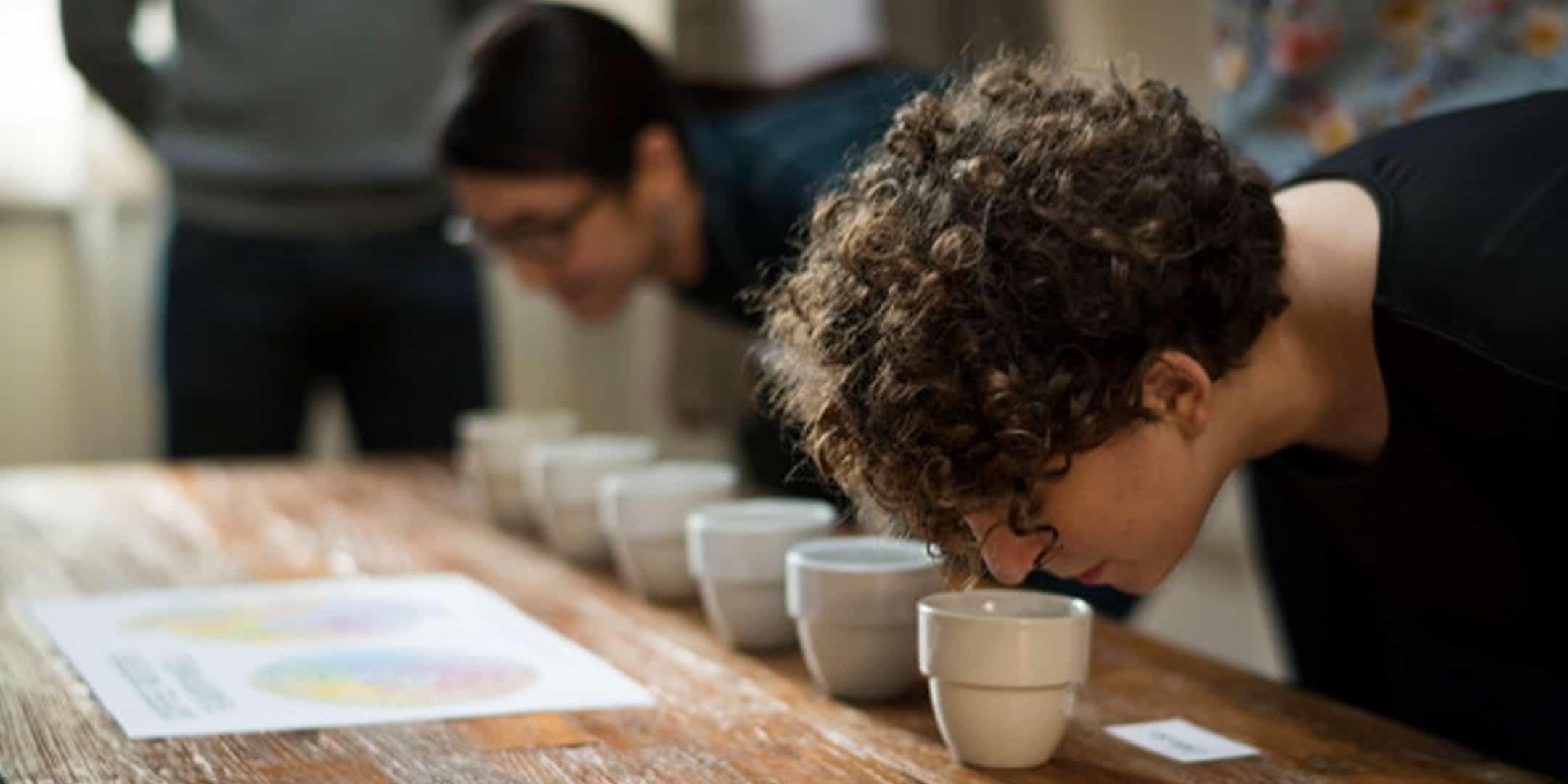 ragazzo che testa dei caffè attraverso la tecnica del coffee cupping