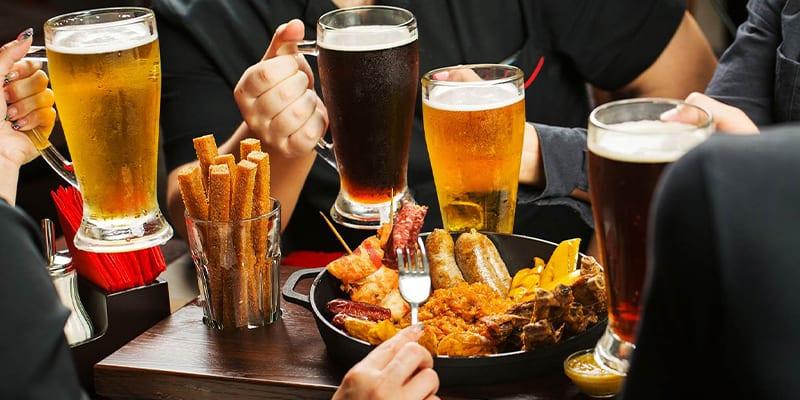 persone che mangiano carne alla griglia con birra