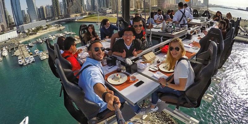 ragazzi che si fanno selfie mentre pranzano su un tavolo sospesi nell'aria