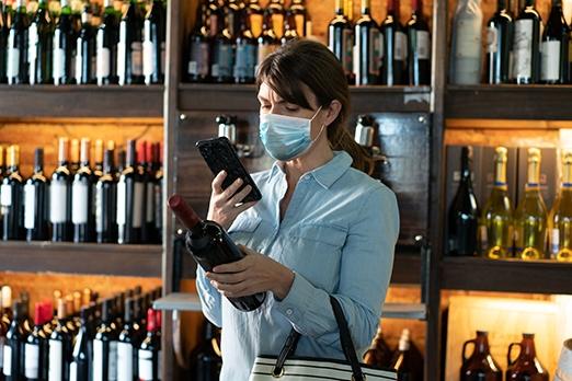 donna con la mascherina che inquadra una bottiglia di vino con il telefono