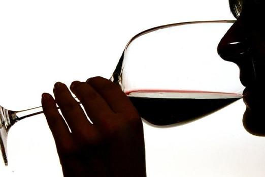 persona che beve calice di vino rosso