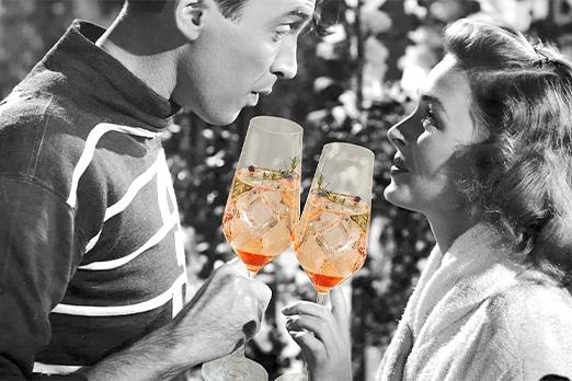 due attori da una pellicola in bianco e nero si guardano negli occhi con un drink in mano