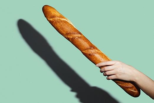 mano femminile che tiene una baguette